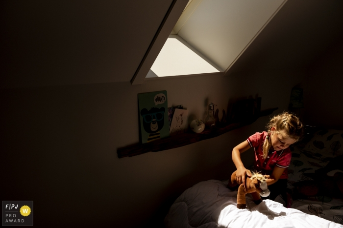 Netherlands Family Photography | young girl playing with a stuffed horse in her room
