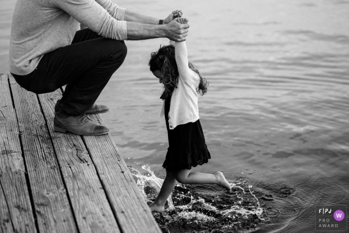 Washington Family Photojournalism | girl kicking her feet as she is held over the water from a dock
