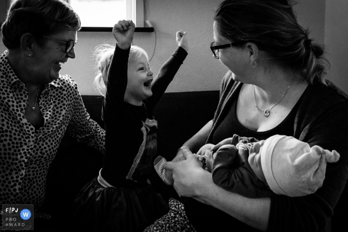 NL family and birth photography in black and white of big sister meeting her new baby brother with extreme excitement