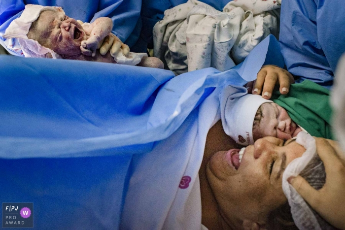 Perinatal Barra da Tijuca birth photograph of a mother smiling after giving birth to twins