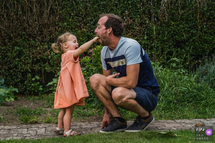 Belgium Family photographer captures this young girl feeding a cookie to her dad