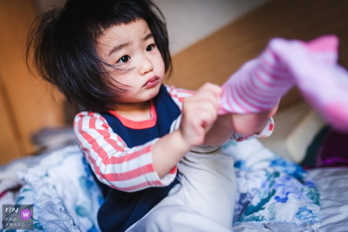 Hunan China family photo of a girl putting on her socks at home