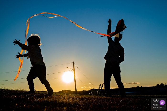 New Hampshire, USA silhouette photo of young boy and father flying a kite