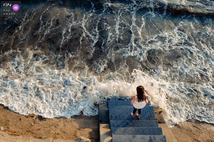 New Hampshire United States family photo of a young girl standing at bottom of steps while ocean swirls around her