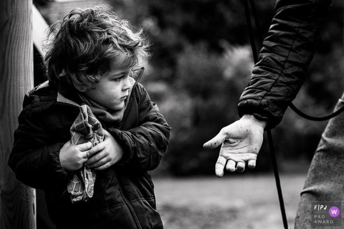 Black and White Wallonie family photos from an outdoor session of child holding back a towl from a reaching parent's hand in Belgium