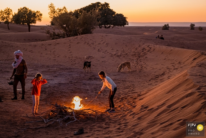 Wallonie, Belgium family photographer documenting a family by a campfire at the dunes in the desert