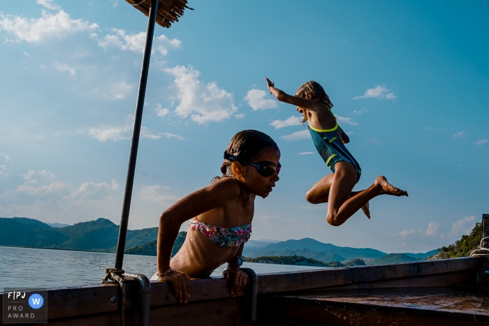 Wallonie family photography session at the water of girl jumping from a dock and one girl climbing out