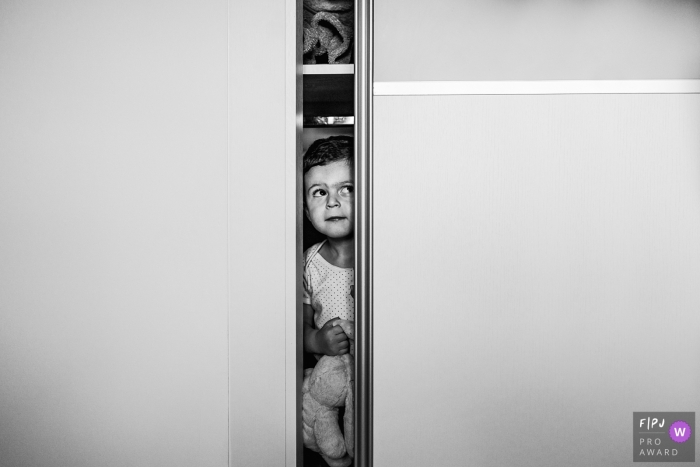County Durham England family photo showing that Hiding in cupboards is so much fun when you're 3