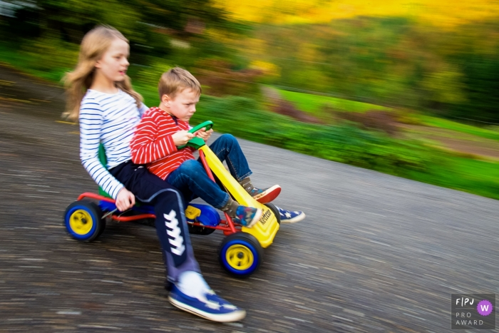 North Rhine-Westphalia family photography showing a Brother and sister on a kettcar in Dusseldorf