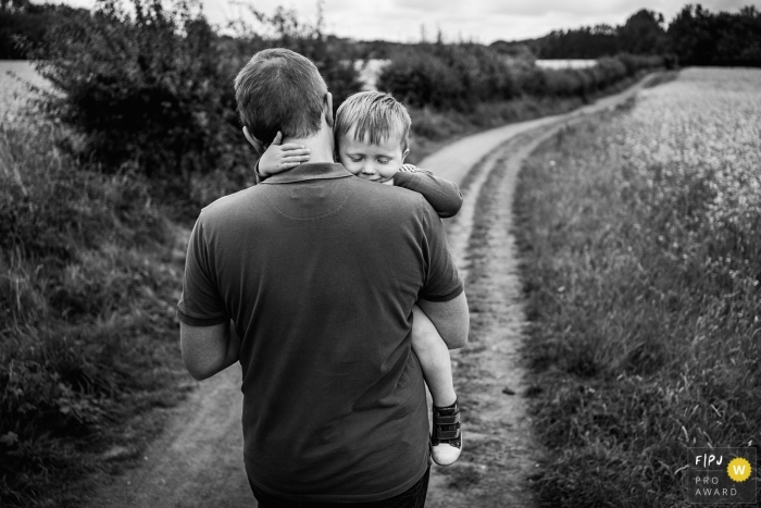 County Durham Sleepy little boy being carried home in a England family photo session outdoors