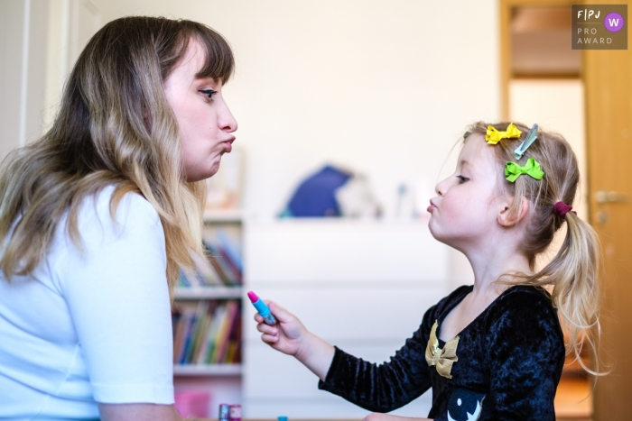 Germany documentary-style family photography session of girl preparing mom to receive some lipstick