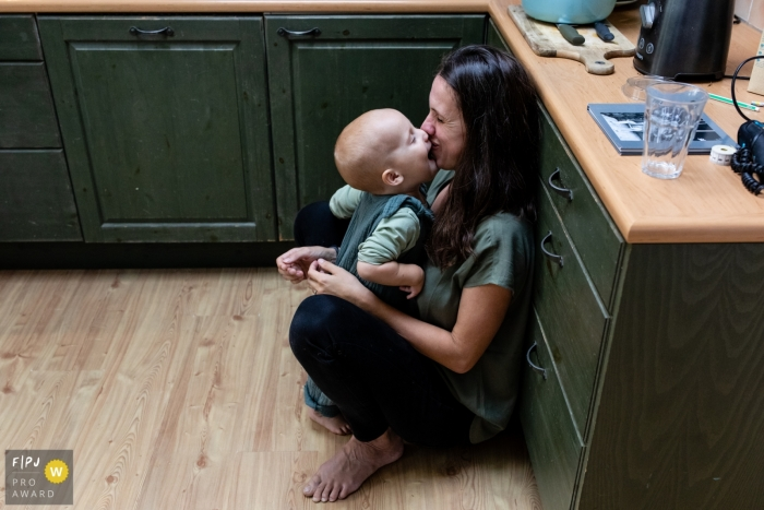 Eindhoven, Noord Brabant documentary-style family photography session capturing young boy giving his mom a kiss in the kitchen