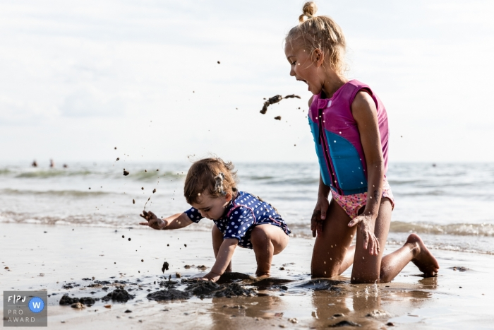 Eindhoven, Noord Brabant family photographer at the beach capturing sisters playing in the sand