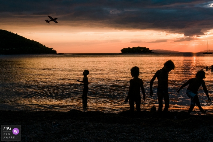 Slovenia family photos from an outdoor, sunset session showing silhouetted children at the beach on holiday