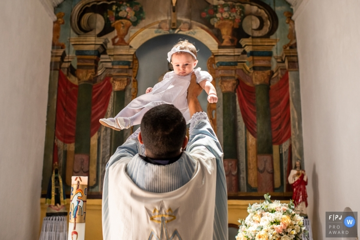 RJ baby baptism photographer captures a young girl being lifted by a priest in Niterói