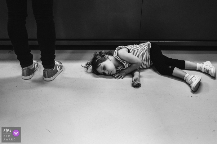 Flanders family photography session image of a girl lying on the ground at the cash register of another shop mom wanted to visit