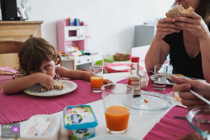 Antwerpen family photographer documents a young girl girl rolling her eyes at the breakfast table in Belgium