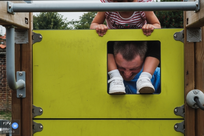 Antwerpen documentary-style family fun photography session in Belgium of a dad taking some suffering while he plays with his daughter at the playground
