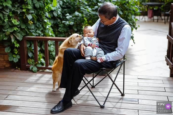 Shanxi outdoor family photography session in the home garden of a baby being held with a very curious dog in China