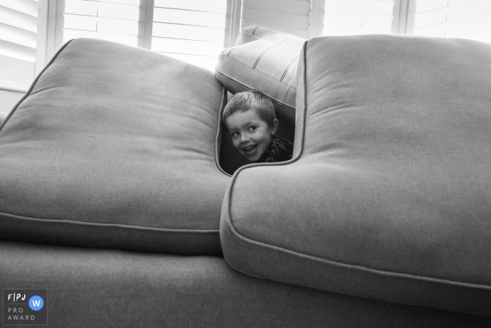 Bath family photos from an at-home session of young boys hiding amongst the sofa cushions in play
