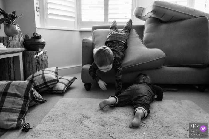 Somerset documentary-style family photography session of brothers playing hide and seek in the sofa in the UK