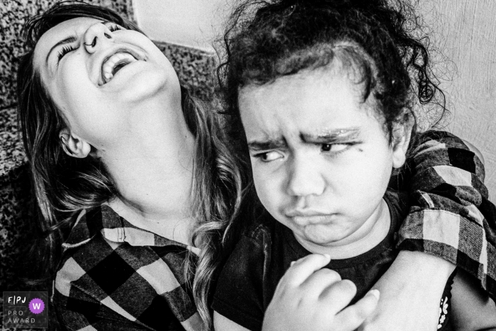 SP, Brazil family photographer captures a mother in laughter as her daughter if expressing opposite feelings