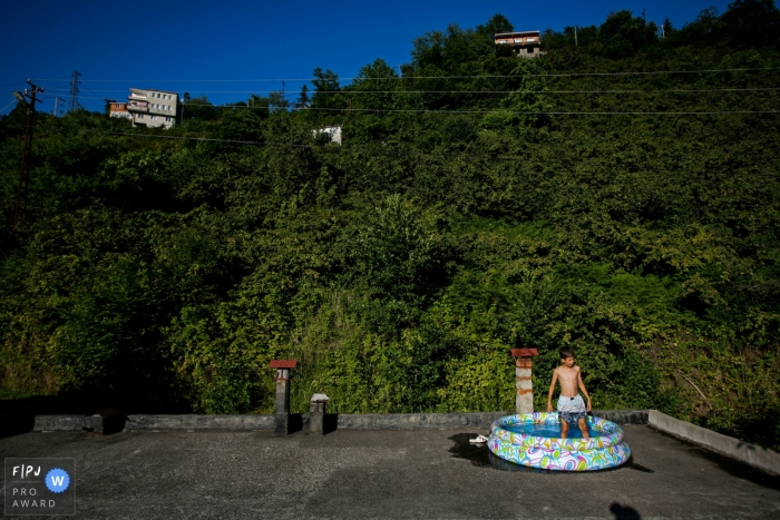 Giresun, Gorele family photography session at the home of a boy in the backyard standing in a pool