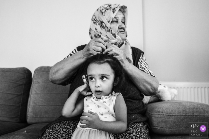 Black and white Istanbul documentary-style family photography session of a grandmother helping out her granddaughter