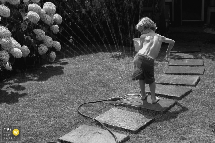 """NB funny family pictures from an at-home photo session by Netherlands Photographer: """"The sprinkler is turned on and everyone is running up and down the garden avoiding the cold beams! except for one: """"come on, what are you waiting for?"""""""