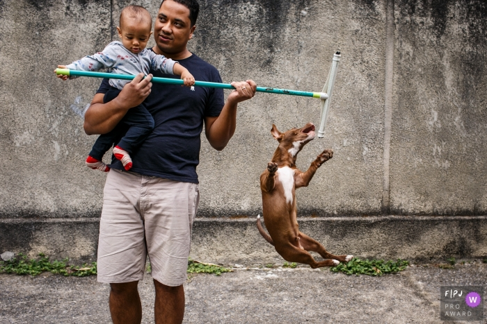 MG outdoor family image session from the home of a dog trying to get the squeegee that the child's father used to clean the yard in Brazil