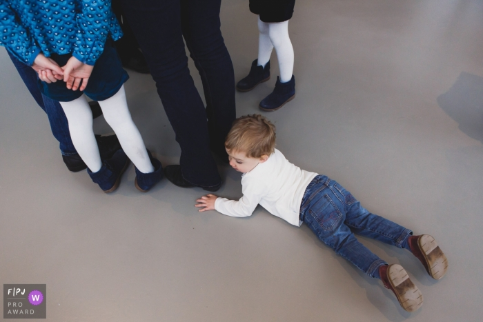 Paris family photography capturing a young boy lying n the floor and you can see the rest of the family's legs standing in a circle