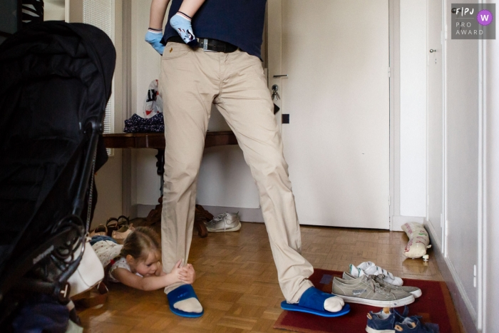 Paris, FR documentary-style family photography session of a young girl slides across the floor holding tight to her father's leg