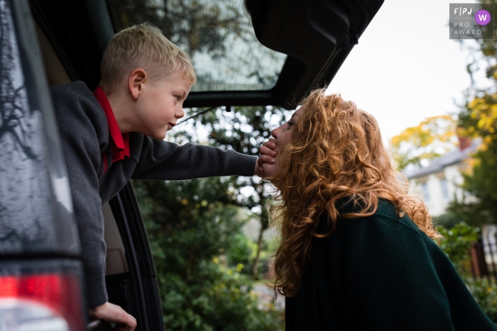Cambridgeshire Family Photo of a young boy reaching out the back of a car while covering his mum's mouth
