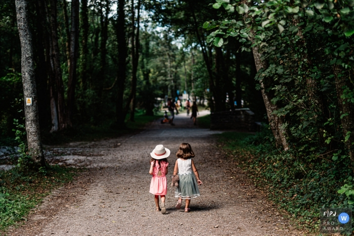 France Family photographer captures two little girls walking down a tree-lined trail