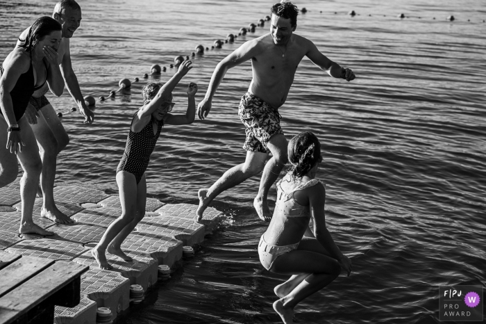 A family jumps into a lake from a dock in this Savoie Family image