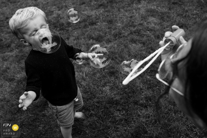 Young boy plays with mom blowing bubbles in this Seattle family photo