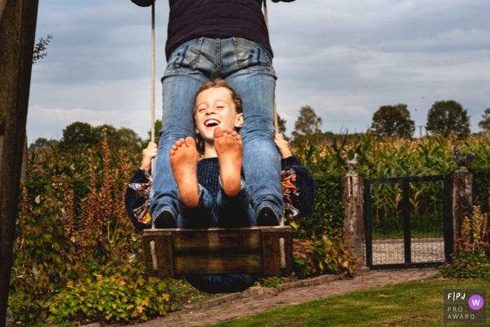 NL family image shoot in the backyard of the home while enjoying the swing with mom to the fullest