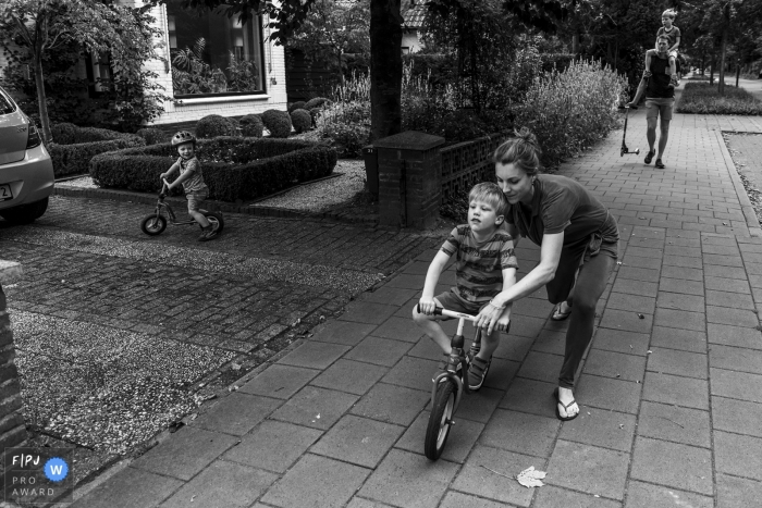 NL outdoor family pictures from an at-home photo shoot of a mother helping her son ride a bike for the first time