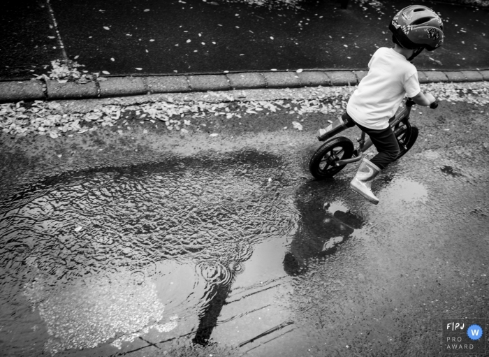 Nimes black and white outdoor family pictures from an at-home photo shoot in Gard with a biking kid in boots