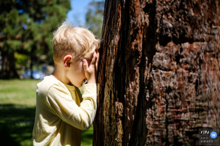 Young boy is playing hide and seek at the park in this San Francisco Family image