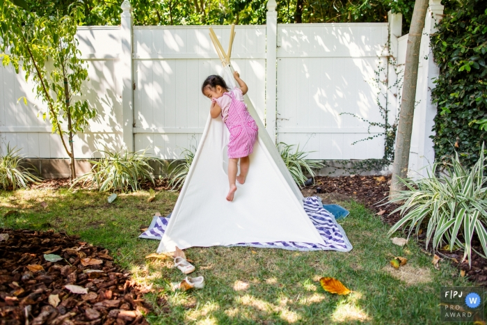 Young girl is documented by a San Francisco Photographer of her climbing up the side a teepee in her backyard camp