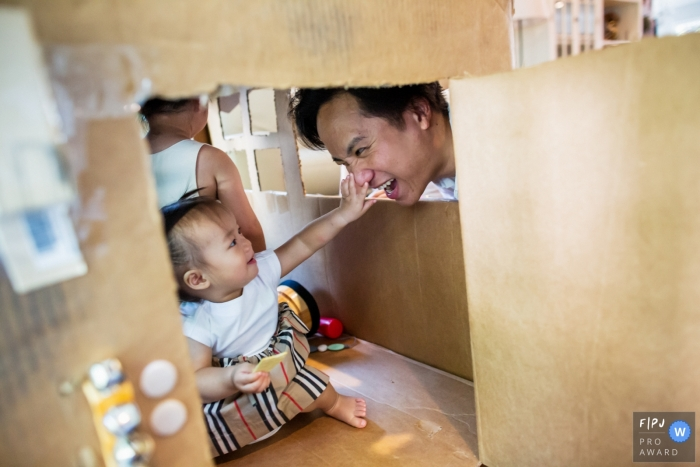 San Francisco Family Photographer captures the playful father looking in on his children and their cardboard box home