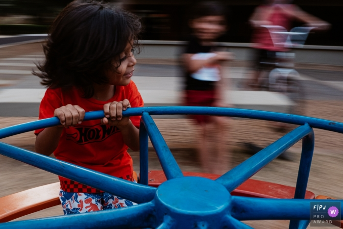 A child spins in a round-a-bout at a park during this Brazilian family photo shoot