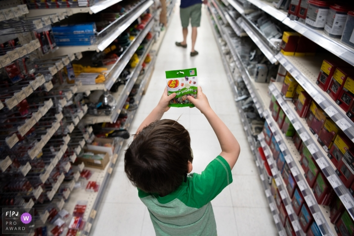 Phoenix Family Photographer captures this boy holding up Jelly Belly's in an aisle at the grocery store