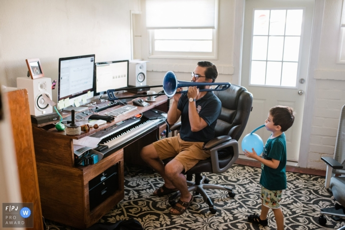 Los Angeles Family Photographer creates this image of a father teaching music class working from home while his son blows up a balloon