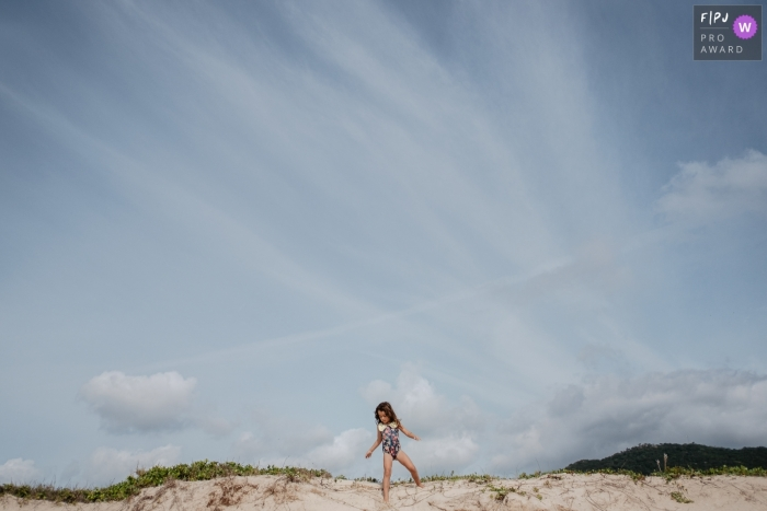 Brazil family photograph of a free girl playing in the dunes of a beach on a beautiful sunny day and blue sky
