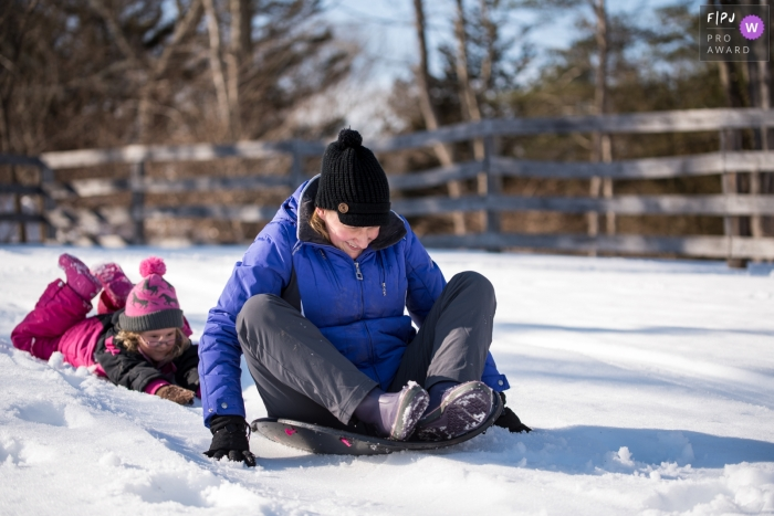 Connecticut Family photograph of a young girl trying to push mom on sled