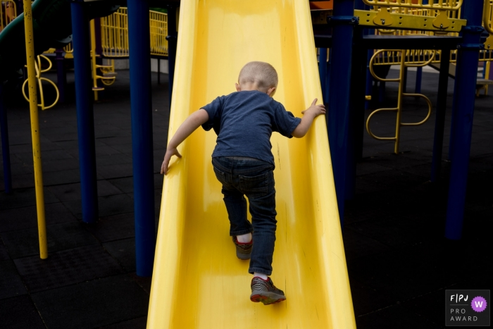 Seattle Family Photographer documents young boy climbing up slide backwards