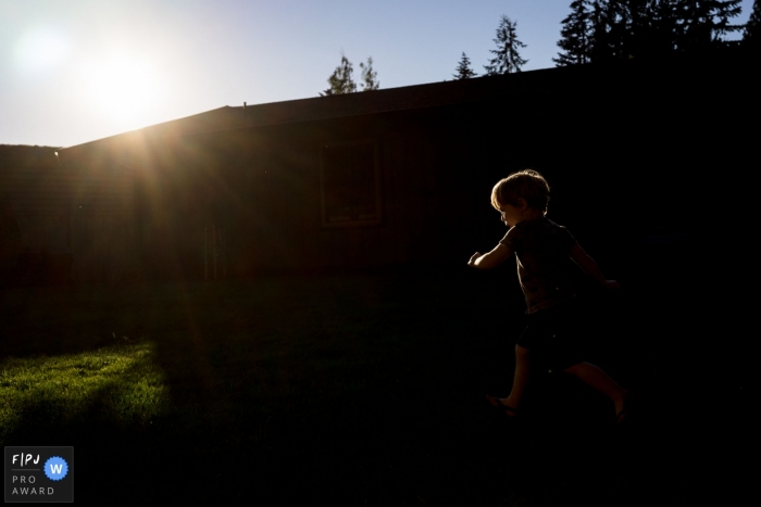 Young boy runs around in backyard in the sunshine in this Seattle Family Photo