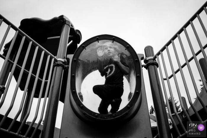 Seattle Family Photographer creates image of kid playing on a park play structure